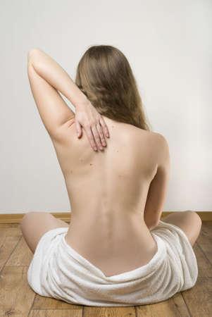 Beautiful blonde Frau sitzen auf dem Boden nach der Einnahme von Spa-Behandlung.