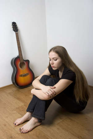 Sad woman with long brown hair sitting on the wooden floor with her acoustic guitar in the background.