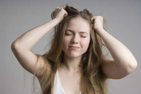 Stress and frustrated woman with hands in her long hair pulling.