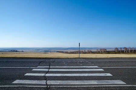 Cracked pedestrian crossing with a picturesque spring landscape as a background. Stock Photo - 9393482