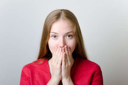 hands covering face: Beautiful woman in a red jacket covering her mouth with hands.