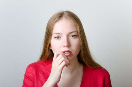 Beautiful pensive woman in a red jacket touching her lips. Stock Photo - 11839860