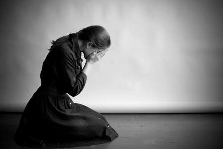 Woman is sitting in profile on an old cracky floor. She is sad and depressed, crying and covering her face with hands. Studio paper  background in behing her. Standard-Bild