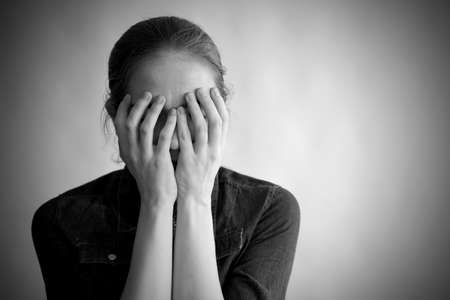 contrast: Monochrome portrait of a depressed woman covering her face with hands.