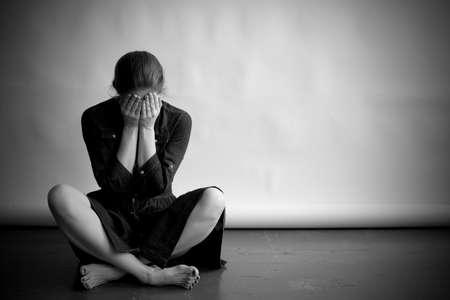 La femme est assise sur un vieux plancher avec des fissures. Elle est triste et déprimé, couvrant son visage avec les mains. fond de papier Studio derrière elle.