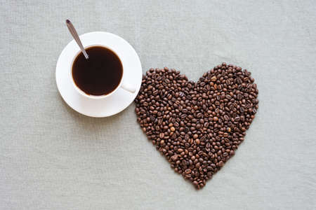 tomando refresco: Heart shape made from coffee beans with a cup of coffee on a grey flax background.
