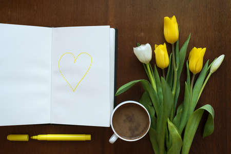 soft tip pen: Tulips and a yellow heart drawn in a book on a wooden table.
