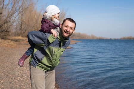 padre e hija: Padre jugando con su hija en la orilla del río Foto de archivo