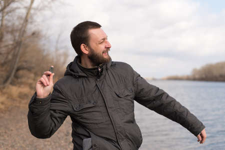 dropping: Man with a beard dropping a stone into the river