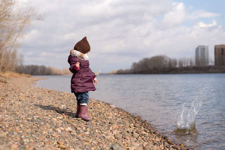 rock hand: Little girl throwing a stone into river on a sunny day