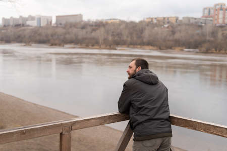 leaning on elbows: Bored man leaning his  elbows on railing and looking at the river