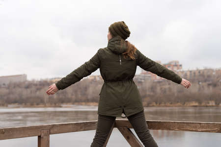 stretch out: Woman stretch out her arms. She is standing at railing and looking at the river on a cloudy day Stock Photo