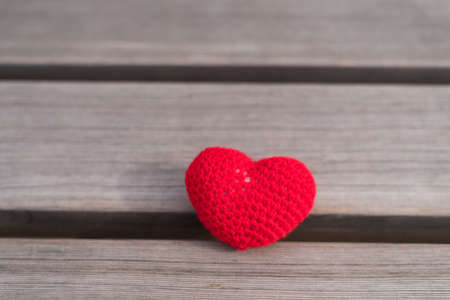 crocheted: Crocheted heart on a wooden board with natural light Stock Photo