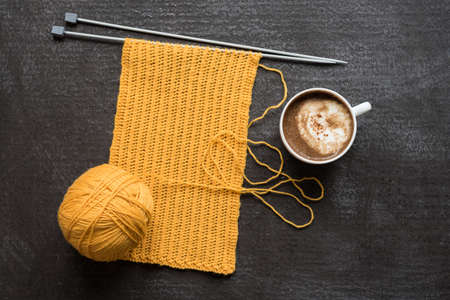 Knitting and a cup of coffee on grunge background.