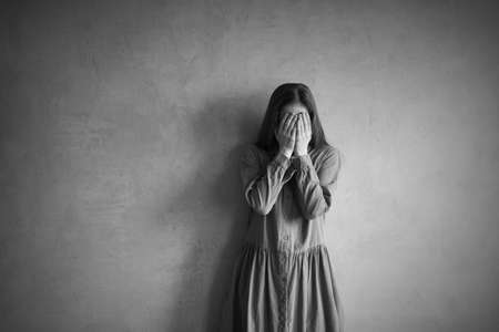Woman is standing hear the grunge wall. She is sad and depressed, covering her face with hands. Retouched and vignette is added.