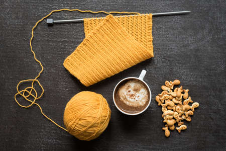Knitting, cup of coffee and fish crackers on grunge background.
