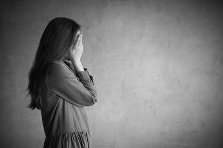 Frau steht die Grunge-Wand hören. Sie ist traurig und deprimiert, bedeckte ihr Gesicht mit den Händen. Retuschiert und Vignette hinzugefügt wird. Standard-Bild