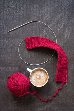 Knitting with red yarn, needles and a cup of coffee