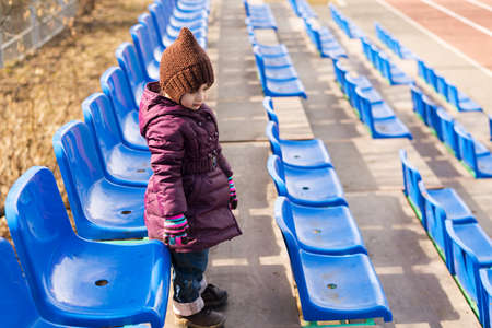 Little girl standing on a viewing stand in spring time