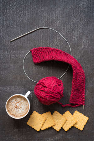 Knitting with red yarn and needles, a cup of coffee and crackers on a dark painted grunge background. Stock Photo