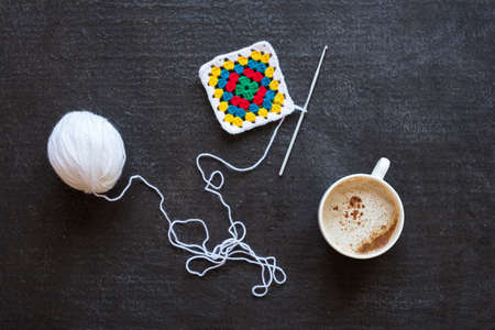 needle laces: White yarn, crocheted multi-colored motif and coffee