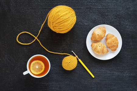 Crocheted element, lemon tea and biscuits on a grunge background.