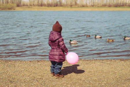 standing stones: Little girl with a pink balloon standing on a riverbank in spring time