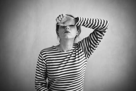 striped vest: Tired woman in a sailors striped vest covering her face with a hand. Retouched image. Vignette is added. Stock Photo