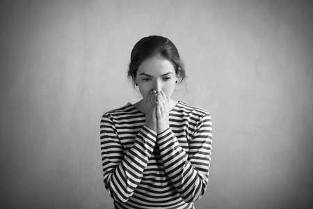 striped vest: Sad woman in a sailors striped vest covering her mouth with hands. Retouched image. Vignette is added.