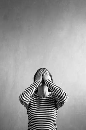 fear face: Vertical picture of a frustrated woman in a sailors striped vest covering her face with hands. Retouched image. Vignette is added.
