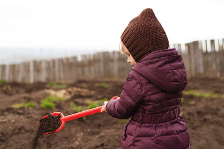 Little girl with a red shovel working in a spring garden.
