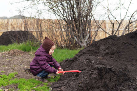 red soil: Little girl with a red shovel working in a spring garden.
