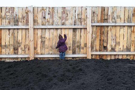 wooden fence: Little girl ploughed field and knocking at the big wooden fence. Stock Photo