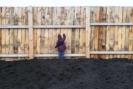 niños negros: Niña campo arado y llamando a la gran valla de madera.