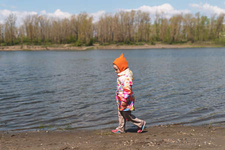pensiveness: little girl walking along the riverbank on a sunny day. Stock Photo