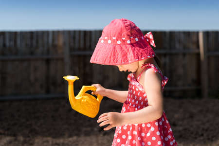 wateringcan: Little girl in a red spotted dress and hat with a yellow toy watering-can in the garden. The day is sunny and the shadow are deep. Stock Photo