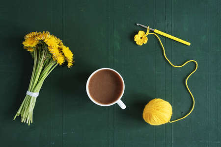 Bunch of dandelions, crocheting and a cup of coffee on a green background.