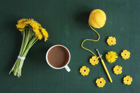 white window: Bunch of dandelions, crocheted flowers and a cup of coffee on green background. Stock Photo