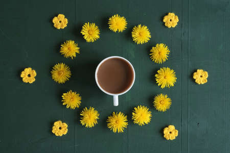 Cup of coffee, dandelions and crocheted flowers on green background.