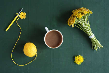 Bunch of dandelions, crocheted flowers and a cup of coffee on green background. Stock Photo