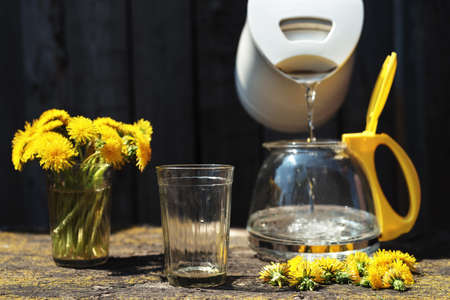deep focus: Making tea with dandelions outdoors at noon. Sunlight is bright and shadows are deep. Focus on a glass. Stock Photo