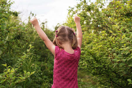 standing up: Little girl standing backward to the camera with her hands raised up on a summer day.