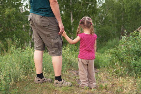 dad and daughter: Father and daughter walking on a hill. They are standing backward to the camera looking at something.