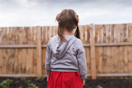 backward: Little girl standing in front of a wooden fence in the garden on a summerday.