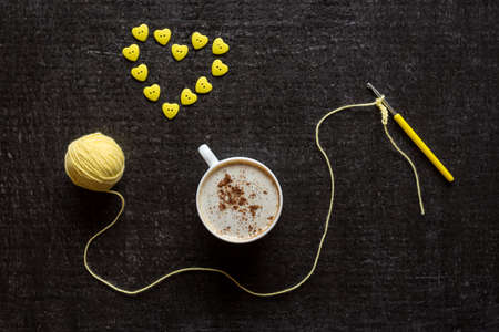 yellow fleece: Cup of coffee, yellow crocketing and a heart made of buttons on a grunge black background.