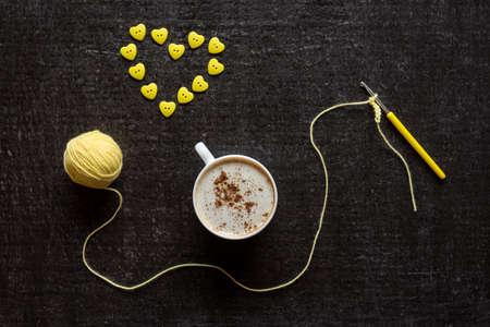 amarillo y negro: Taza de café, crocketing amarillo y un corazón hecho de botones en un fondo negro del grunge.