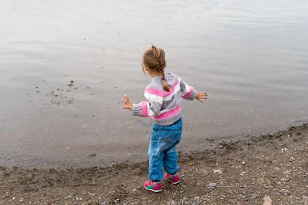 niñas jugando: Niña de tres años de edad en un suéter y pantalones vaqueros lanzando pequeñas piedras en el río.