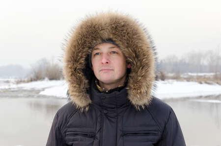 fur hood: Portrait of a man in a fur hood on a winter background.