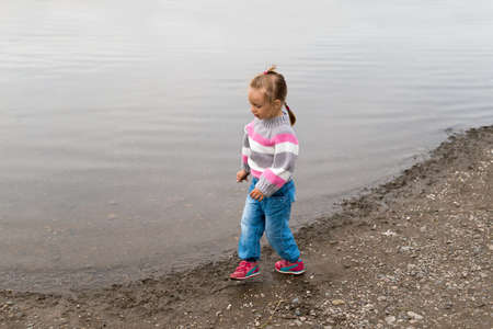 Girl walking on the river bank. She is wearing a sweater and jeans. She is looking like she is dancing and singing os saying something. Stock Photo