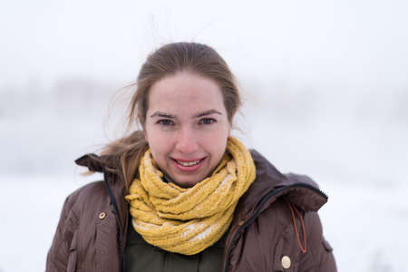 unzipped: Portrait of a smiling woman in winter. She doesntt have a hat, her coat if unzipped, soft focus is used.